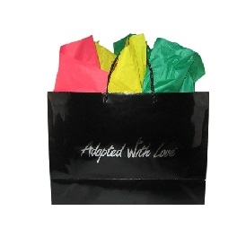 Black gloss adoption gift bag with green, yellow and red tissue paper, ready for Ghana adoption gifts